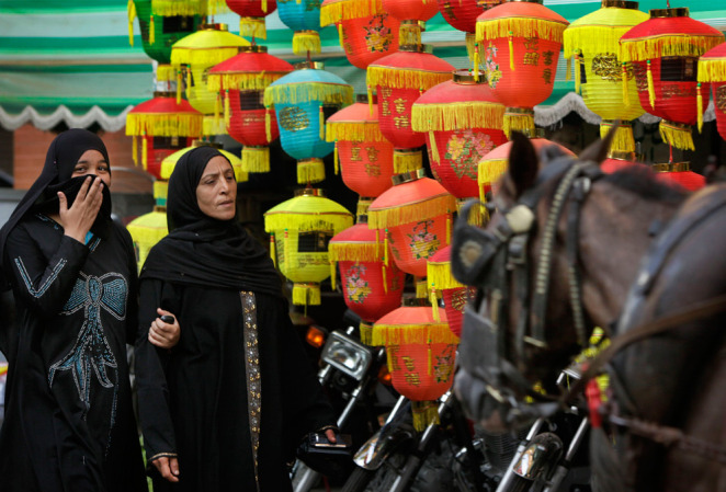 Egyptian women walk past paper lanterns used as for Decoration khotba